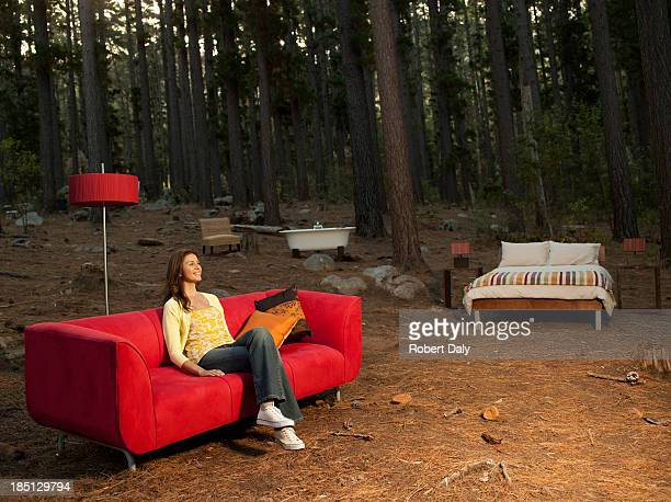 A woman with home furnishings sitting outdoors in the woods