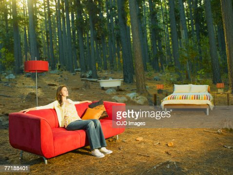 A woman with home furnishings sitting outdoors in the woods : Stock Photo