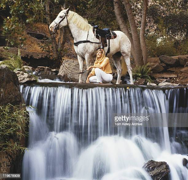 Woman with horse near waterfall