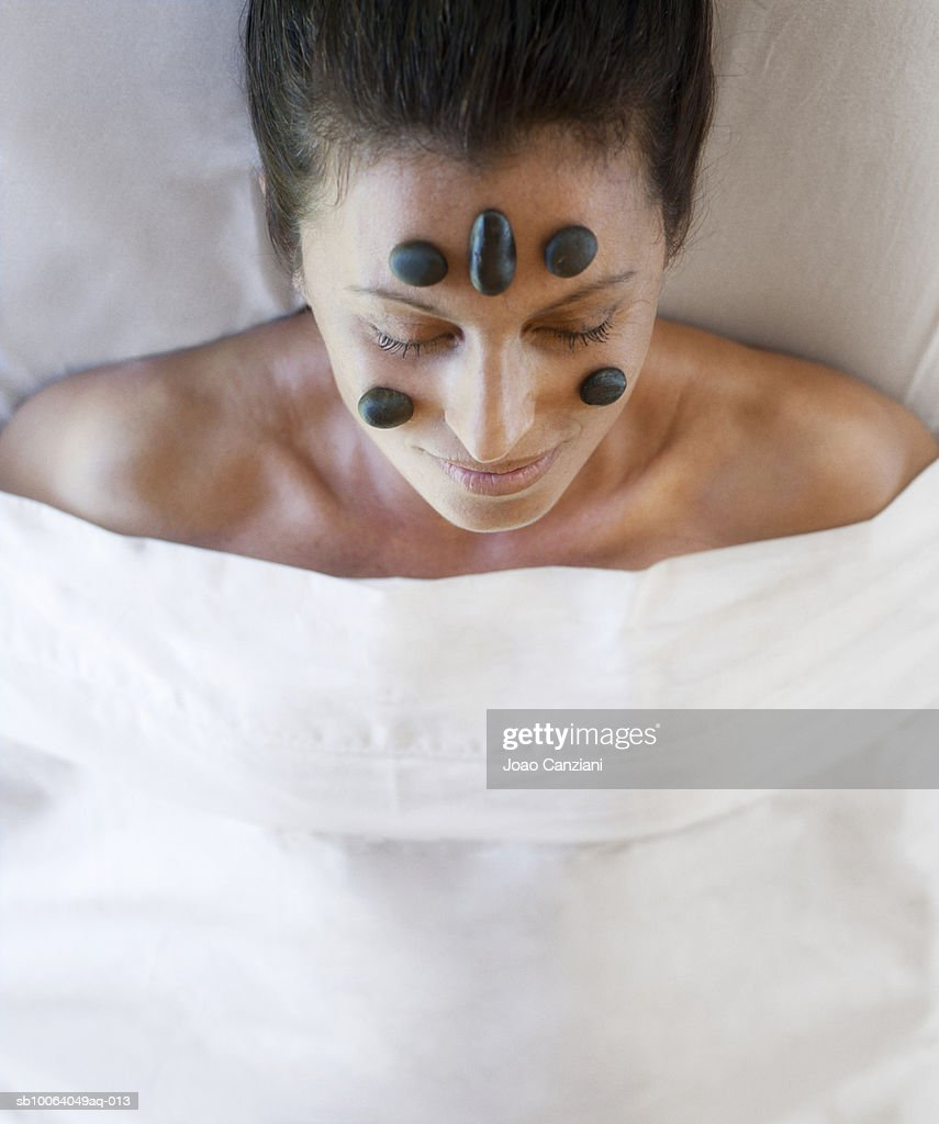 Woman with hot stones arranged on face lying down, elevated view : Stock Photo