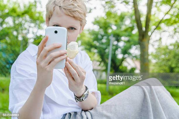 Woman with ice lolly in her hand taking selfie with smartphone