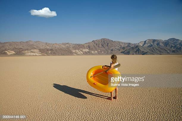 Woman with inflatable dinghy in desert, rear view