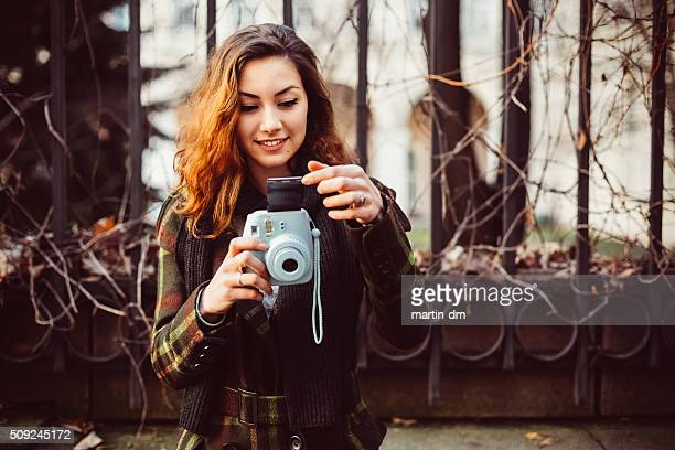 Woman with instant camera outside