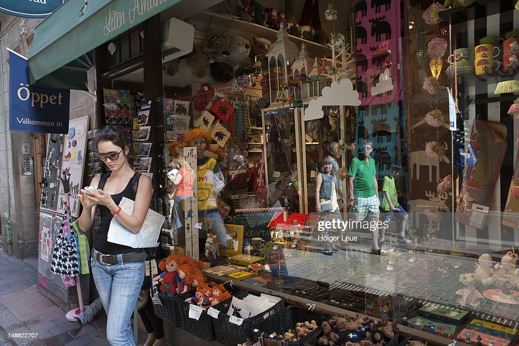 Woman with iPhone outside souvenir shop in Gamla Stan old town. : Stock Photo