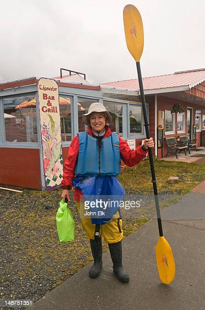 Woman with kayaking gear and paddle.