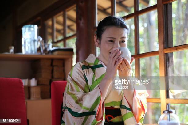 Woman with kimono drinking coffee in cafe