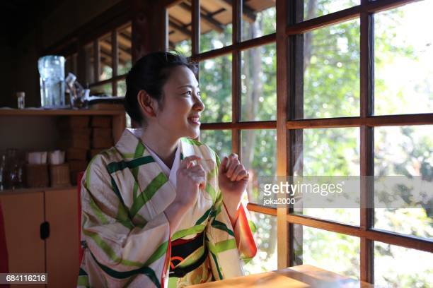 Woman with kimono smiling in cafe
