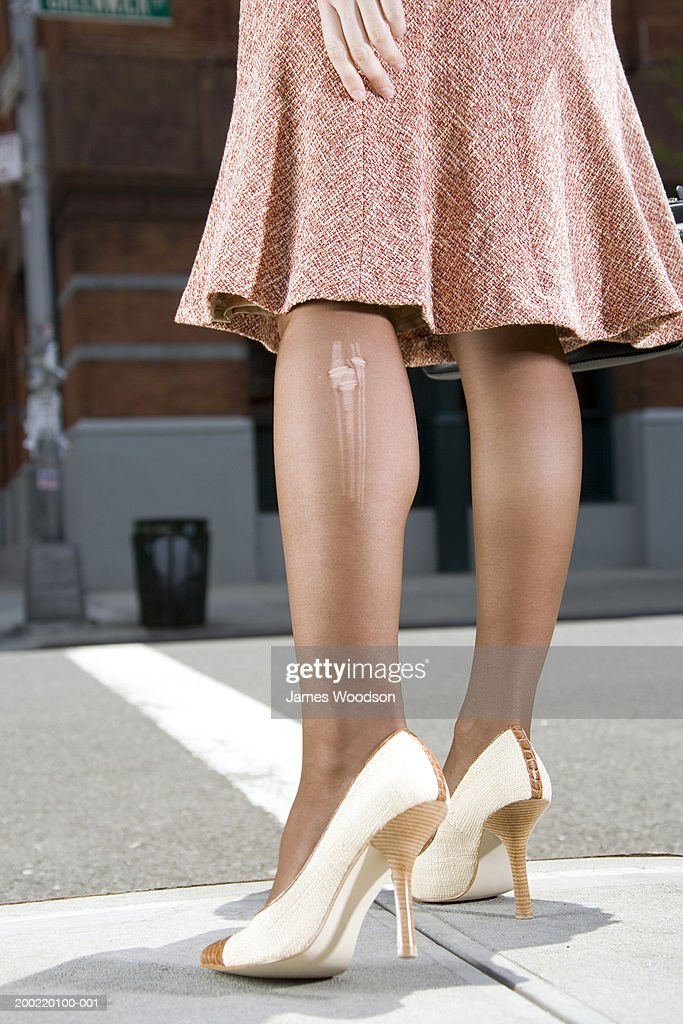 Woman with laddered stockings standing at roadside, low section : Stock Photo