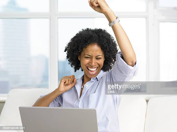 Woman with laptop and arms in air, smiling