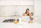 Woman with laptop and breakfast