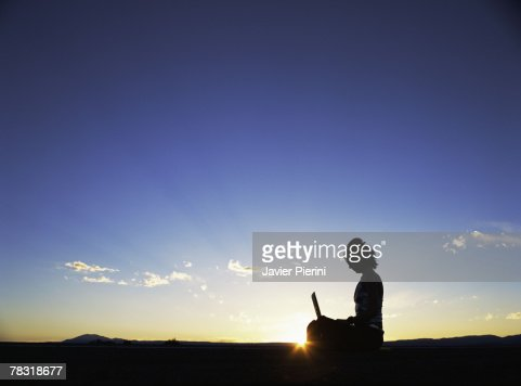 Woman with laptop at sunset : Stock Photo