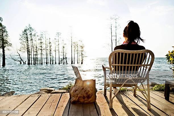 Femme avec ordinateur portable sur le lac