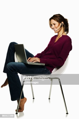 Woman with laptop computer and earpiece : Stock Photo