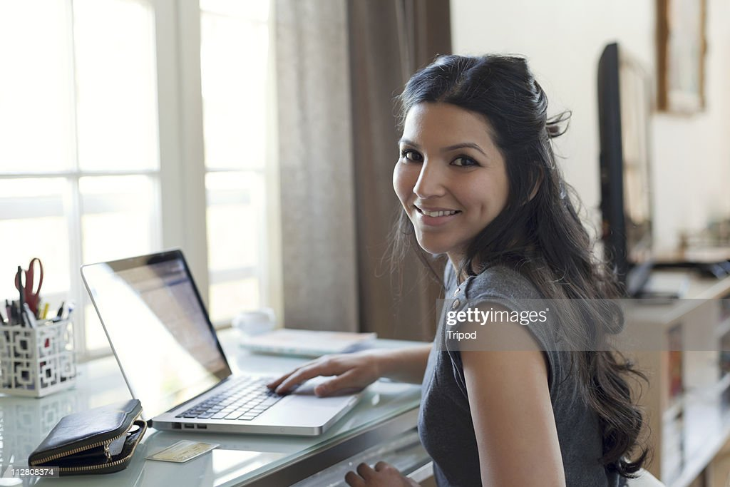 Woman with laptop, credit card and wallet, smiling : Stock Photo