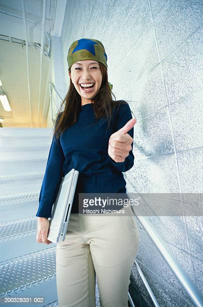 Woman with laptop holding thumbs up, portrait