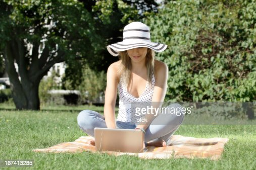 Woman with laptop in park : Stock Photo