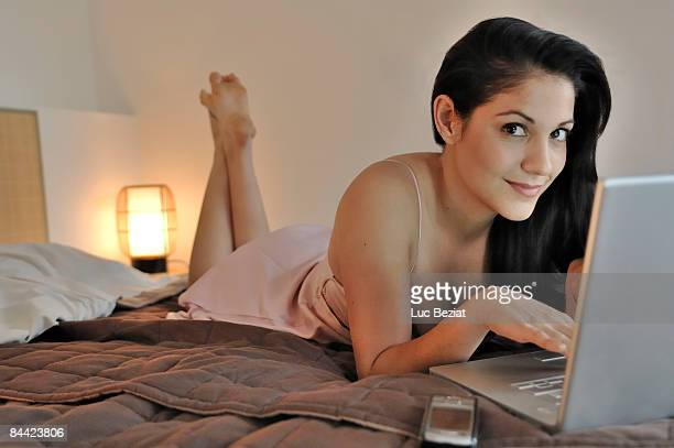 Woman with laptop on bed