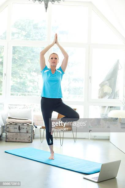 Woman with laptop practicing yoga on gym mat in living room