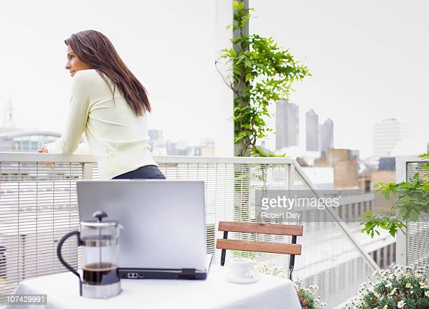 Woman with laptop standing on city balcony