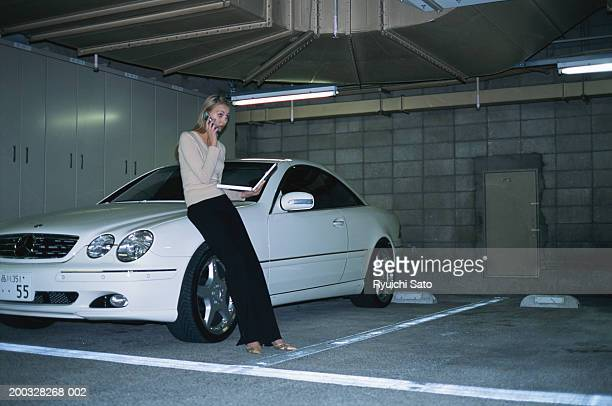 Woman with laptop using mobile phone by car
