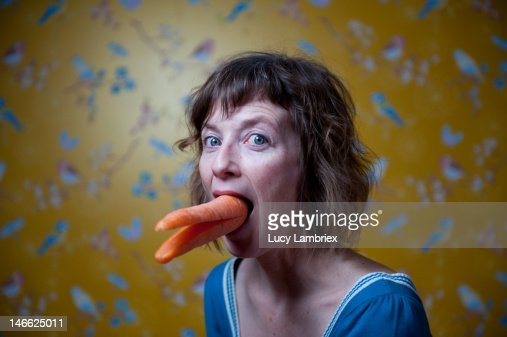 Woman with large carrot in her mouth : Stock Photo