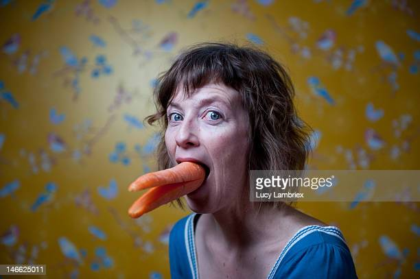 Woman with large carrot in her mouth