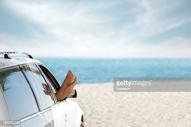 Woman with legs out off car window on beach