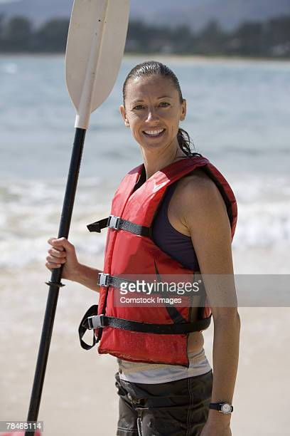 Woman with life vest and paddle on beach