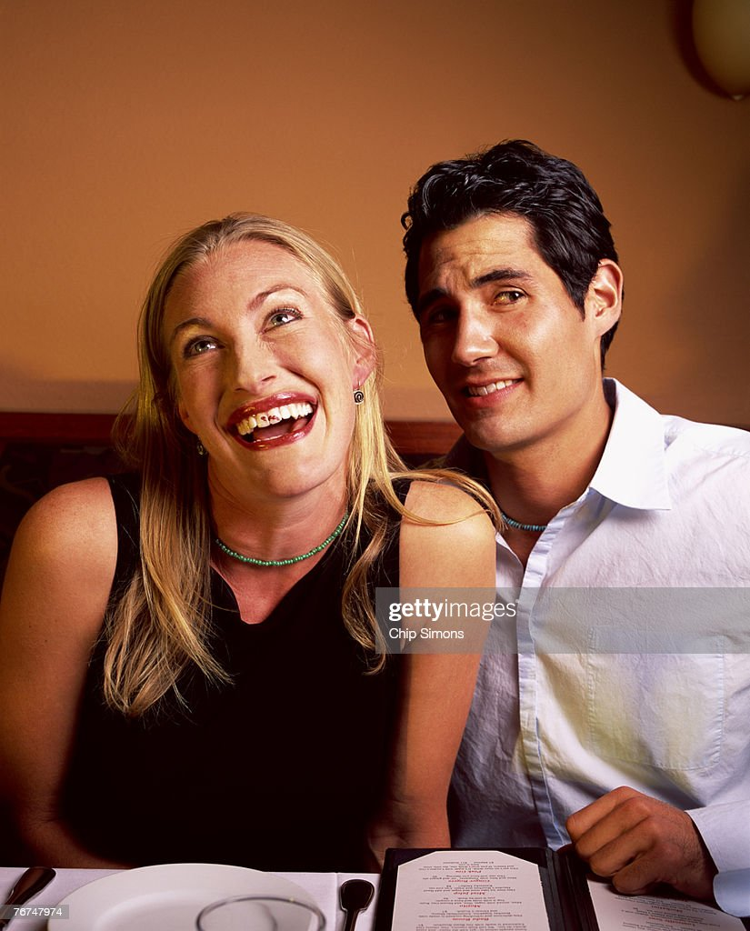 Woman with lipstick stain on teeth with man : Stock Photo