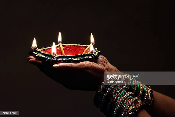 Woman with lit earthen lamp at Diwali festival,India.