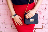 close up woman with little black bag in stylish outfit red skirt and black blouse