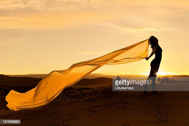 Woman with long billowy scarf with sunset backdrop