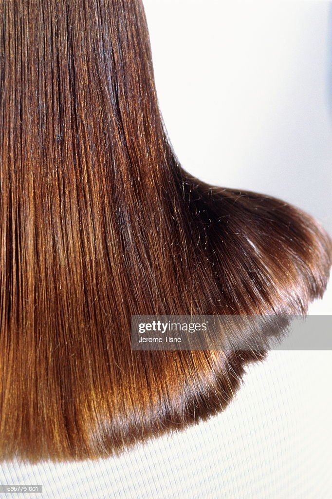 Woman with long brown hair falling across shoulder,back view,close-up