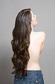 Woman with long brown wavy hair, rear view