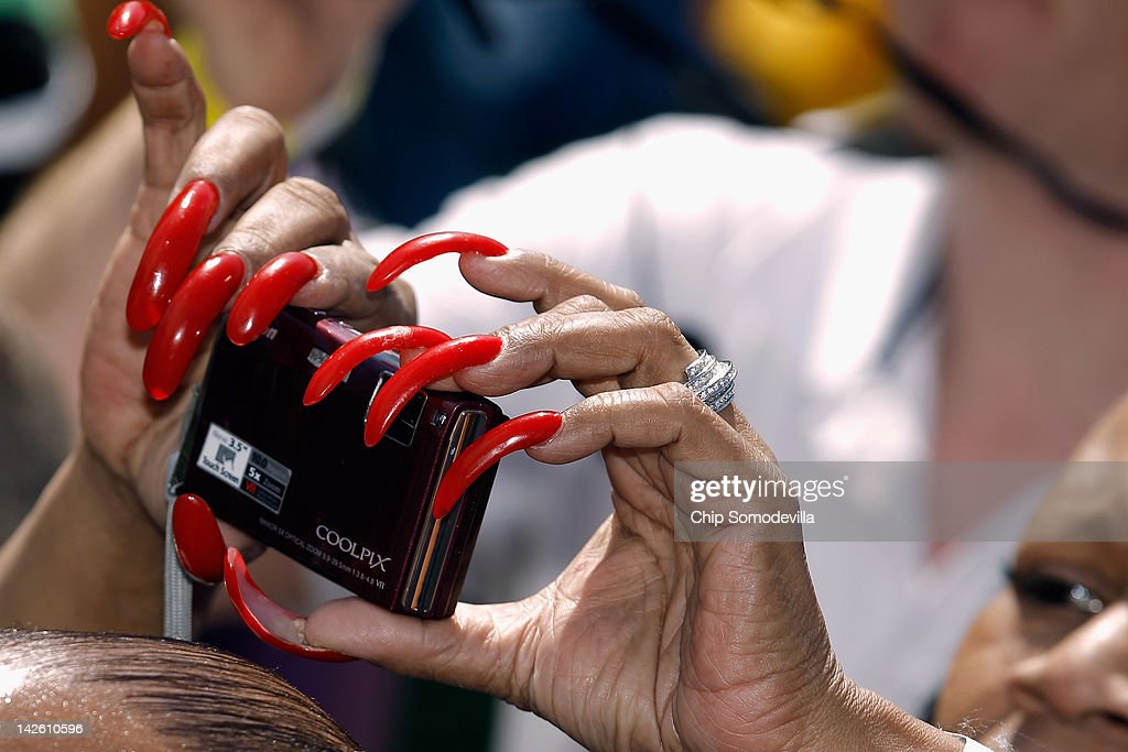 A woman with long fingernails takes photographs of U.S. President Barack Obama during the annual Easter Egg Roll on the South Lawn of the White House April 9, 2012 in Washington, DC. Thousands of people are expected to attend the 134-year-old tradition of rolling colored eggs down the White House lawn that was started by President Rutherford B. Hayes in 1878.
