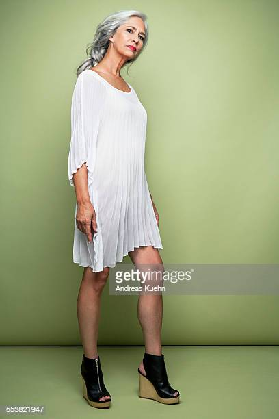 Woman with long, grey hair in platform heels.