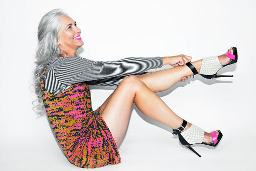 Woman with long, grey hair sitting and laughing.