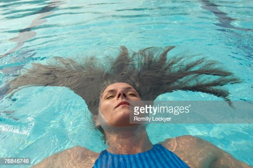 Woman With Long Hair Floating In Swimming Pool Eyes Closed Stock Photo Getty Images
