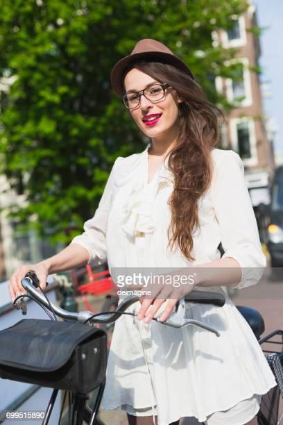 Vrouw met lange haren op fiets in de straten van Amsterdam