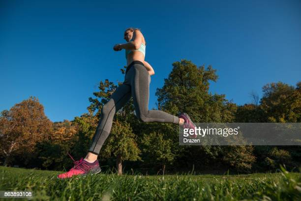 Woman with long legs running in forest in summer