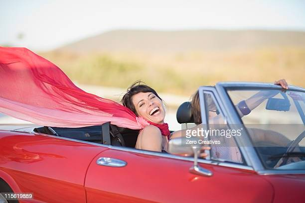 Woman with long red scarf riding in car