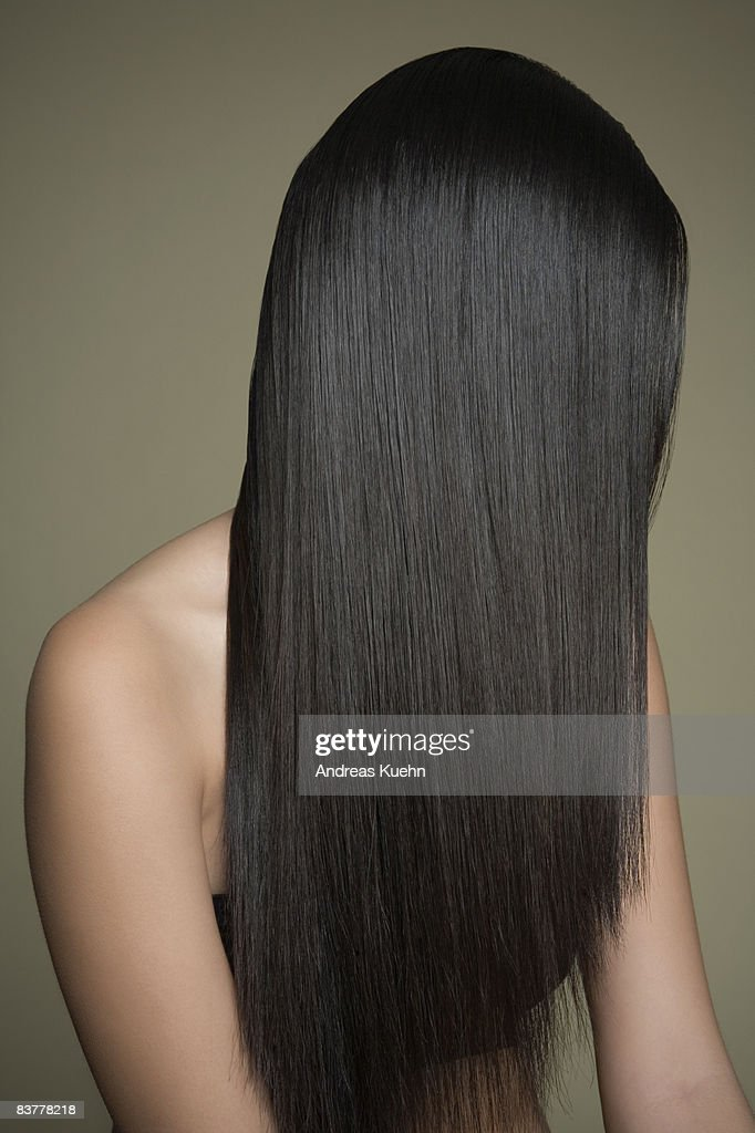 Woman with long, shiny hair covering face. : Stock Photo