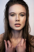 Portrait of young woman with beautiful face and eyes, natural make-up, pretty long wet hair, hands on her hair and drops of water on her face, looking at camera