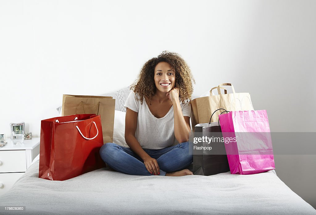 Woman with lots of shopping bags sitting on bed : Stock Photo