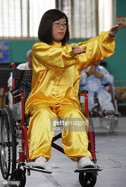 A woman with lowerlimb disabilities sitting in wheelchairs plays Tai Chi Chuan in Xuanhua District on July 15 2015 in Zhangjiakou Hebei Province of...