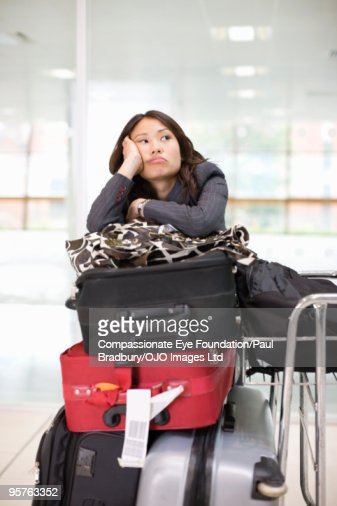 Woman with luggage waiting in airport  : Stock Photo
