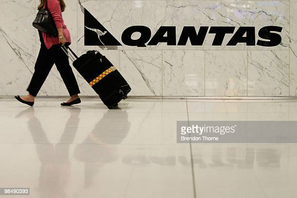 A woman with luggage walks past a Qantas sign as flights are delayed and cancelled following the eruption of iceland's Eyjafjallajokull volcano at...
