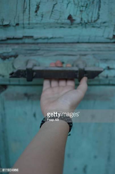 Woman with macrame bracelet opening the door