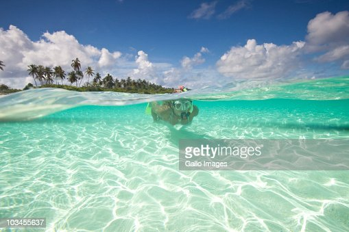 Woman with mask, fins and snorkel diving in ocean, Kadhdhoo Island, Laamu Atoll, Southern Maldives, Indian Ocean