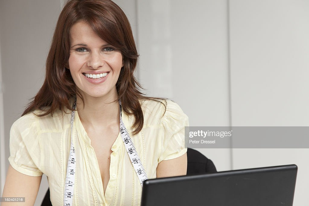 Woman with measuring tape around neck using computer : Stock Photo